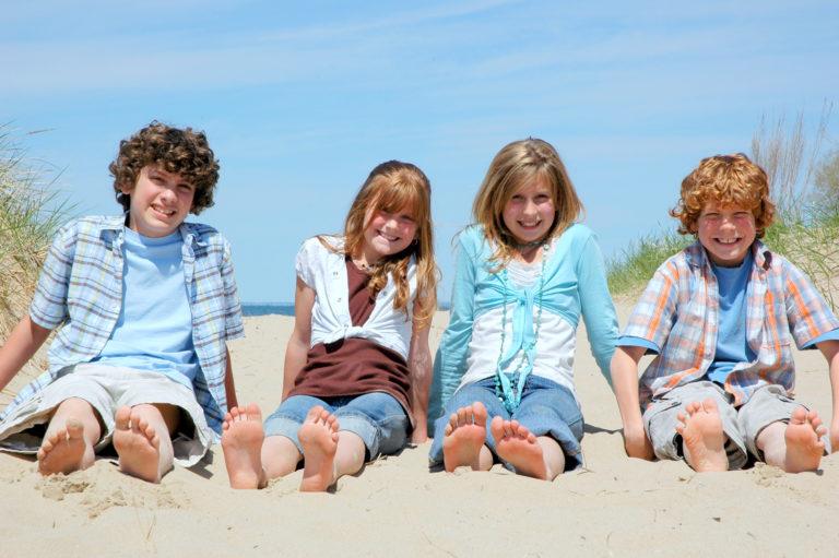 Fyra barn sitter barfota på stranden